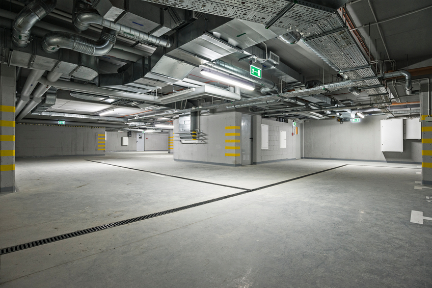 Empty, new, underground parking garage interior. At the ceiling is located electrical system and air condition.