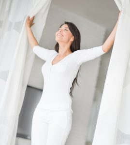 Peaceful woman at home opening the window and enjoying fresh air