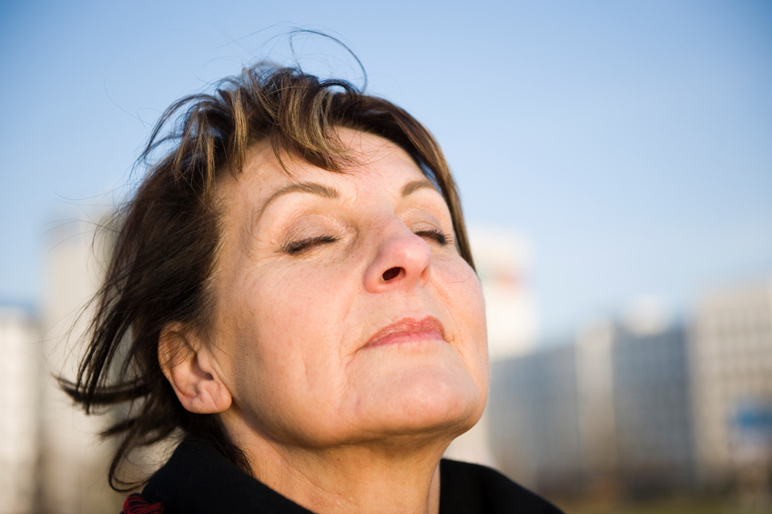 lateral head portrait of a mature woman in Fuzzy urban light deep breathing with eyes closed