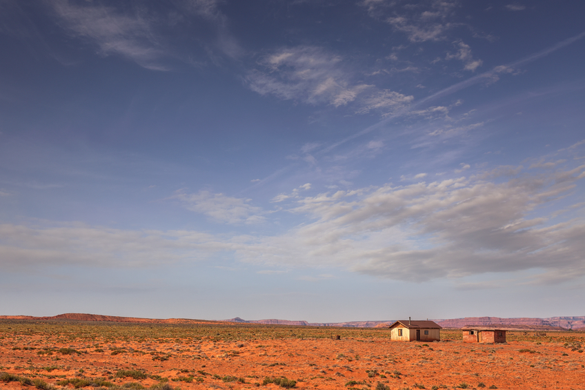 A small house with an outhouse in a barren desert landscape (Utah).